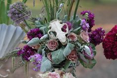 """To add a New Orleans voodoo vibe, we have yet another unique arrangement with our rustic animal skull. A beautiful, and more muted arrangement, with pops of color, using a dusty rose """"Amnesia"""", lavender stock, fuchsia stock, serocina (pitcher plant),lavender herb, dusty miller, allium, and purple cabbage."""