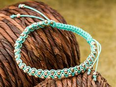 Knot Me Bracelet 1mm turquoise Chinese Knotting cord in the center of the folded strand, you will be working with two strands in the center. Make a square knot around the two center strands and then thread some TOHO 6/0 bead. working from 2 center cords,move right bead and know half your sq knot, pull left bead, tie last part of sq knot. cleaver!