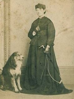 c. 1861- 1862 CDV photograph of an young English woman from the East Midlands woman with her canine companion. Her habit is transistional in style between 1850's and 1860's fashions. The bodice is still cut slightly longer in length than what was fashionable during the 1860's but still retains a long 1850's style basque and peplum.