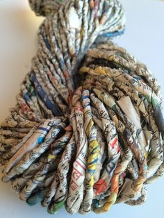 Handmade hand twisted newspaper yarn from recycled newspapers. A unique ethical yarn which is magical for jewellery making, weaving, basket making and fibre arts. It has been made especially for Yarn Yarn by a womens co-operative in India from newspaper waste. The colours, the chunky texture, the writings. It really is simply a marvellous yarn. Indian newspapers and a lovely print with colour! This listing is for 1 x 100g approx 45 - 50 yards. We also have other weights and yardage of this…