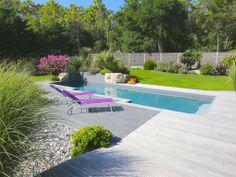 La piscine paysagée par l'esprit piscine - 8 x 3,5 m Revêtement gris clair Escalier d'angle intérieur avec mini banquette Margelles en granit noir flammé