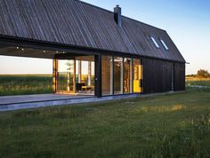Enflo Arkitekter's simplistic Gotland Summer House on the Swedish island in the Baltic Sea emulates the region's barns and features sliding louvered walls that open the structure to the land on each side.