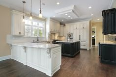 Kitchen with half white cabinets and half black cabinets on dark wood floor with white ceiling in newly constructed home.