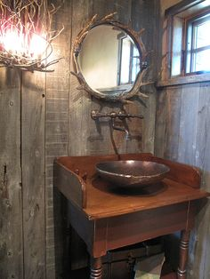 Rustic reclaimed wood, elk antler mirror, twig wall sconce, and great hardware in this log powder room bath.