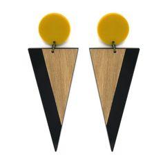 Brinco longo com base de acrílico mostarda redonda e pingente de acrílico em formato de triângulo invertido na cor preta com detalhe sobreposto em laminado de madeira clara.Medidas do brinco (AxL, incl. base): 9,5 x 3,5 cm.Referência: V17-827Esse...
