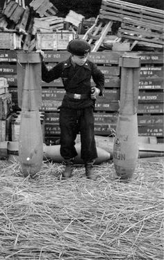 This child soldier is wearing the uniform of Panzer troops. He's measuring himself against aerial bombs, 1944.