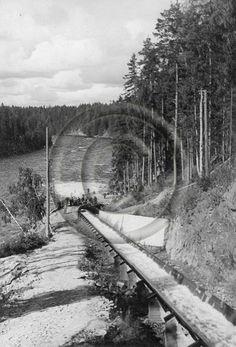 Pyhäkosken uittoränni. Uittorännin alapäässä seisoo miesjoukko.   Pyhakoski Timber Slide. = from The Finnish Forest Museum