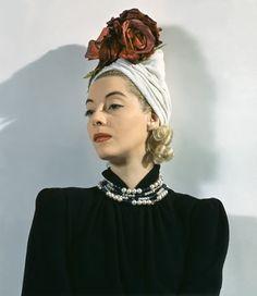 Model wearing white clipped velvet turban with red velvet rose,1941.