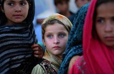 Afghan refugee children waiting in line for a ration of rice.