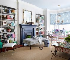 Contemporary living room features a navy fireplace mantle topped with a white and navy seashell encrusted mirror flanked by tall freestanding metal bookshelves. Arranging Bookshelves, Cool Bookshelves, Fireplace Bookshelves, Bookshelf Styling, Fireplace Mantle, Vintage Fireplace, My Living Room, Living Room Decor, Living Spaces