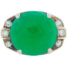 1930s Art Deco Jade Diamond White Gold Ring. Elegant Art Deco cocktail ring created in the 1930's. Features an oval cabochon jade accented with three diamonds on each side set in white gold. The jade measures 13.56 x 12.84 x 6.88 mm. C 1930s
