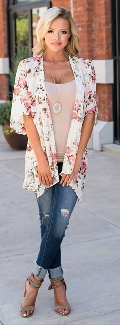 #spring #outfits woman standing with cross legs wearing white and pink floral open cardigan and distressed blue denim jeans. Pic by @shopmvb