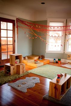 Me encanta que es un lugar que invita a entrar y quedarse, o sea, yo quiero jugar ahí! Fíjate que hay muchos elementos en madera, todo al tamaño y alcance del niño. Los guindalejos podrían tener lucesitas de colores de navidad, así de noche no es tan oscuro. Montessori genius.