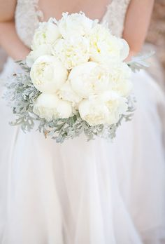 Brides.com: All-White Wedding Bouquets. A romantic bouquet made of peonies and dusty miller styled by Lucy Munoz.
