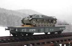 "WWII German StuG III Ausf B transported on a DR 50 ton Flat Wagon Type SSys ~ WWII German Deutsche Reichsbahn railways (DR) 50 ton heavy 4-axle 2 Rail ""O"" Scale wagon type SSys transporting a StuG III Ausf B tank."