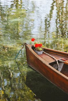 Beautiful wood boat with red flowers on a lake.