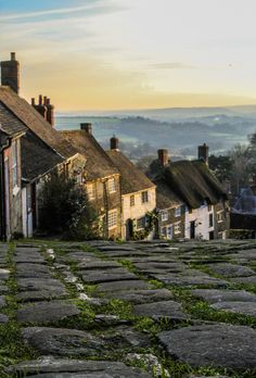 Sweetly cobbled street-somewhete in the UK(I could be wrong,but something about the gold light,green fields,& blue mist just seem to whisper that this street is on one of those dear little islands that collectively make up the United Kingdom..if I had to guess which one,i'd say..England.?)-If anyone can ID this street/town/locale,I would be delighted to know its name!