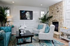 Contemporary living room with turquoise blue velvet tufted sofa and gray slipper chairs with Kelly Wearstler Katana Pillows in Teal separated by modern espresso coffee table filled with white canisters over graphic turquoise rug.