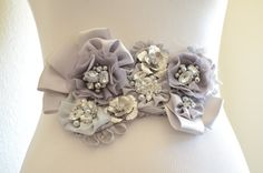 A Beautiful One of a Kind sash in grey made from satins, chiffons, crystal rhinestones, Swarovski rhinestones. Would be a great addition to your Special Day.