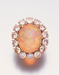 A water opal and diamond dress ring, French, circa 1960 Claw-set with a large cabochon water opal, within a border of brilliant-cut diamonds, diamonds approximately carats total Opal Jewelry, Jewelry Rings, Jewelry Accessories, Fine Jewelry, Jewellery, Antique Jewelry, Vintage Jewelry, Dress Rings, Opal Rings