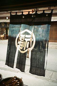 暖簾 Noren are hung at the shop entrance welcoming customers