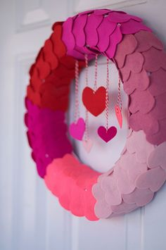 """Open Your Heart to Me"" Wreath. All you need is:  1 wreath form  Fabric or ribbon to wrap the wreath form  A hot glue gun  Felt in assorted colors  Baker's twine  5 straight pins"