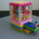 This candy dispenser provides a fun way to get a delicious sweet treat. A simple slider mechanism doles out the goods and the top has an easy-release lid. The Lego ...
