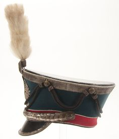 SIDE VIEW OF AN IMPERIAL RUSSIAN OFFICER'S SHAKO OR KIVER FOR AN AIDE DE CAMP. Model 1907 'Bell crown' shako with black leather top, royal blue wool rise and red band, piped in white, and black leather visor, with silvered eagle plate, chin scales and visor trim, as well as a cockade and horsehair plume. Complete with silver bullion crown braid and cords. Lined in black fabric and leather sweatband. - Jackson's International Auctioneers and Appraisers