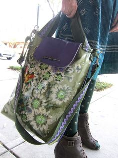 vintage embroidery cover by clear vinyl and lined in purple leather and green rick rack. awesome travel bag.