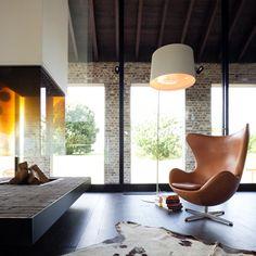 Un grande camino è il fulcro dell'abitazione, si tratta di una struttura sospesa alta sei metri realizzata in acciaio e, nella parte che sovrasta il focolare a legna, è composta da lastre di vetro che lasciano spaziare liberamente lo sguardo per tutto il living. photo © Tim Van de Velde