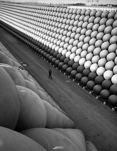 """A security guard walking down US Highway 101 where there are towering stacks of hollow iron floats from which the iron antisubmarine nets were suspended to protect the US ports during the last war."" Life"