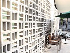 Locally manufactured ventilation blocks, arranged like a Chinese lattice screen, create a breathable wall that shields the house from the harsh evening sun.