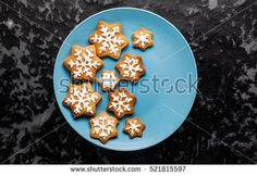 Christmas cookies in the form of stars with frosting on a plate, on a dark background.