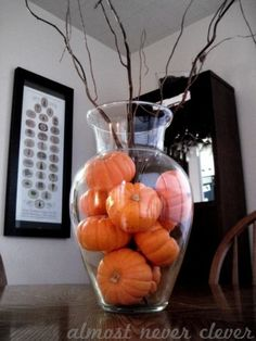 Small artificial dollar store pumpkins in the base of a dollar store vase with dollar store branches. Perfect and cheap fall decor for around the house or in guest bath!