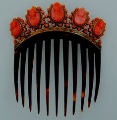 Magnificent example of a French Empire shell comb from the Eugenie period, circa 1860. The brass gallery underneath the cameos is intricately inlaid. The 5 ox-blood coral cameos are superbly carved and surrounded by coral beads.
