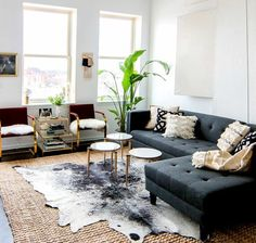 salon avec plante verte, canapé gris, tapis en peau de vache, coussins décoratifs, beige, noir, blanc, table de salon