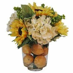"""Silk sunflower and hydrangea arrangement in a clear glass vase with faux water and lemons.  Product: Faux floral arrangementConstruction Material: Silk and glassColor: Yellow, creme, green and brownFeatures: Includes faux hydrangeas and sunflowersDimensions: 12"""" H x 12"""" Diameter Note: For indoor use only"""