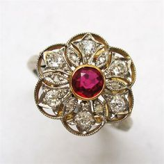 A RUBY AND DIAMOND CLUSTER RING OF PIERCED FLORAL DESIGN MODERN BUCCELATTI