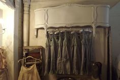 Using a neat vintage headboard or footboard from a bed to display clothes in a store.