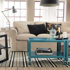 The elements in a neutral room are drawn together with a pair of bright, mobile coffee tables. | Coffee table in dark turquoise, IKEA PS 2012 @IKEAUSA