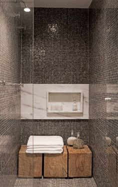 Love this..exactly what I'm looking for, for small shower stall...shower, grey mosaic tiles, wooden stools (love those instead of a built in bench), glass panel door, lighted shower head, built in shelf for shampoo, etc..