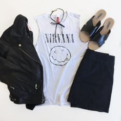 A band tee with a choker necklace, a moto jacket, a denim skirt, and slide sandals