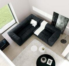 un canapé noir d'angle et un tapis blanc dans le salon