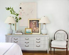 Painted in a soft shade of gray, the dresser nearly disappears against the bedroom wall. The large abstract artwork is by Molly Ledbetter, the portrait is by Minnette's maternal grandmother, and the nautical scene is by Sam Barber, a family friend.