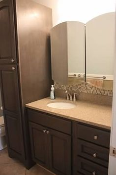 Remodeled bathroom - view from door. Double medicine cabinets, glass & stone mosaic tile backsplash, quartz vanity top, & Haas cabinets in Teal on maple