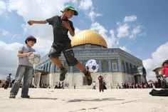 A young boy plays with a soccer ball in front of Jerusalem's Dome of the Rock mosque. (Ahmad Gharabli / AFP / Getty Image)