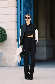 LE FASHION BLOG PARIS STREET STYLE VARSITY MINIMAL BY VANESSA JACKMAN LOW BUN BLACK VARSITY JACKET WHITE SLEEVES BLACK CROP TOP HIGH WAIST W...