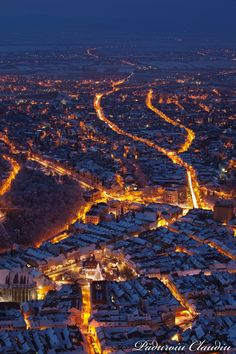 Brightly lit city streets at night in Brasov, Romania.  snow, trees, town, from the air above