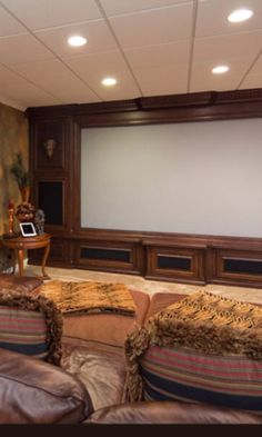 Media room with huge screen framed by wood-paneled wall and large overstuffed sofa.