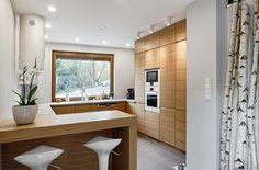 Küche in G-Form mit Halbinsel in Weiß und Holz